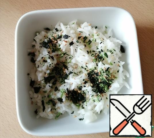 Boil the rice, if it is already cold, then warm it up by washing it with boiling water. It turned out that I did not have nori and I sprinkled rice with other algae, but this did not affect the taste, only the taste of sesame was added.