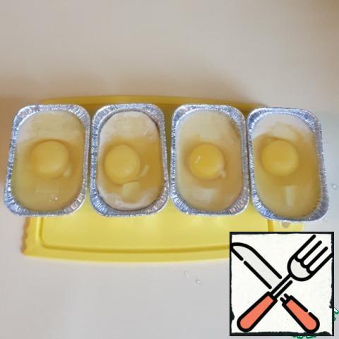 In each mold, break an egg, add salt to taste, you can optionally loosen the yolk.