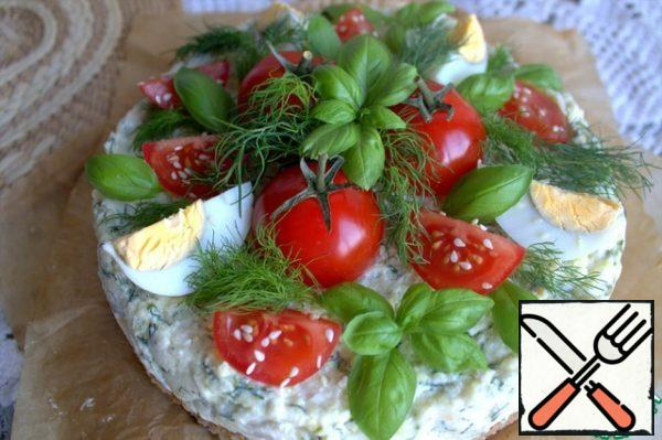 Decorate the frozen cake with a cut egg, tomatoes and herbs.