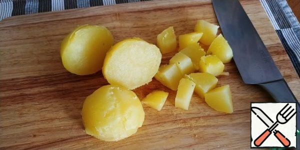 Boil 2-3 potatoes (the author has 1), in the peel until ready, cool, clean, cut coarsely.