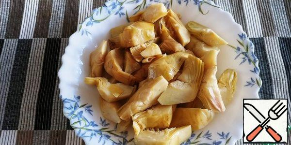 We decant artichokes from the oil. In the original, they are fresh, but now, alas, it is not the season.