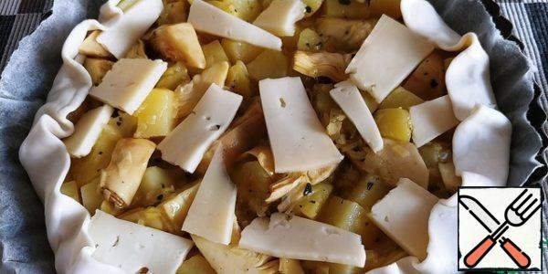 We begin to collect the pie. We spread the puff pastry with paper on a 24-26cm form, then potatoes with onions and egg, we randomly lay out artichokes on top. The top layer is placed in the spread of cheese.