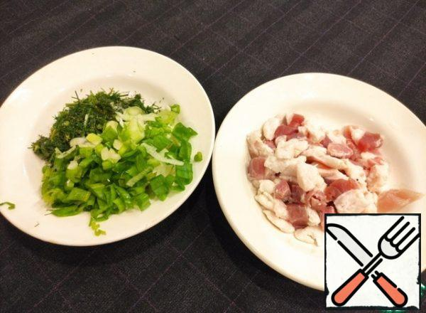 Cut the fat into cubes not finely, about 1 cm, cut the greens, onion in half rings.