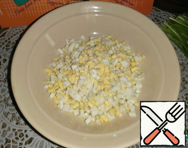 Boil the eggs, cool and cut into small cubes.