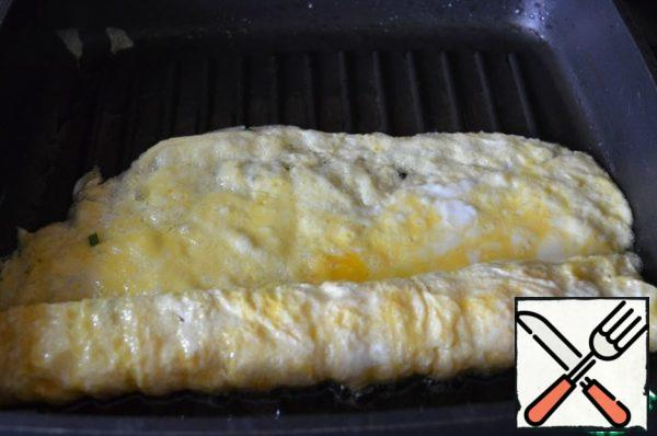 """Carefully twist the roll, leaving a small """"tail"""" of the omelet, it is convenient to do this with a wide silicone spatula. I still twisted, but the photo did not work out, alas..."""