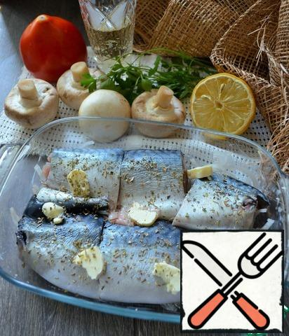 Clean the fish, remove the head, tail and fins. Cut the fillet from the bone, cut into portions. Grease the refractory mold with butter, put half of the onion (half rings) on the bottom, spread out the fish, add salt, season with savory and spread out the pieces of butter.