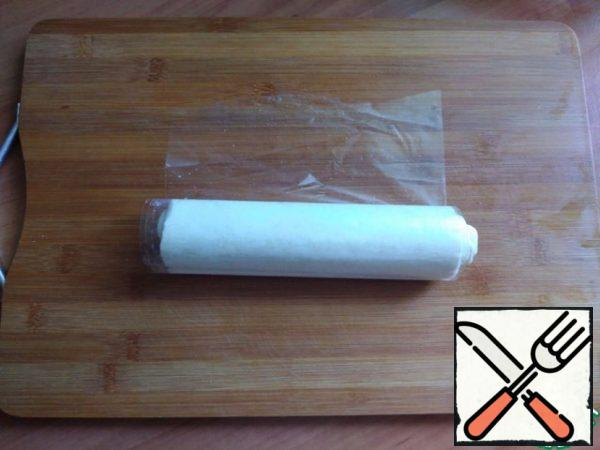 The dough has defrosted. Download puff pastry into a tight roll.
