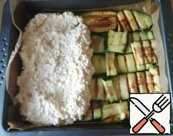 Place half of the zucchini on a baking sheet or a suitable form. The second layer is the curd-cheese filling. The third layer is again zucchini.