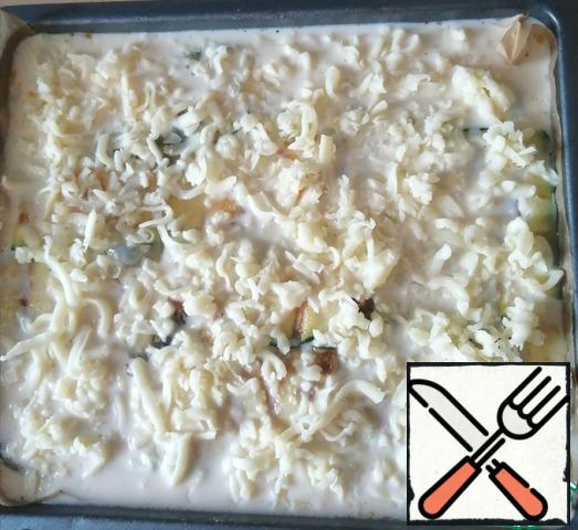 Pour the egg-milk filling and sprinkle with cheese. Preheat the oven and bake for 30 minutes at a temperature of 200 degrees until golden brown.