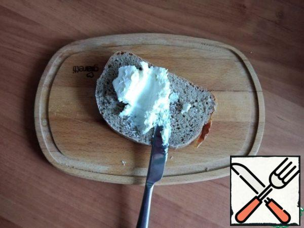 For serving, I will use a thick wooden board. We begin to collect Smerrebred. A thick layer of cottage cheese cream cheese is also spread on a thick piece of rye bread.