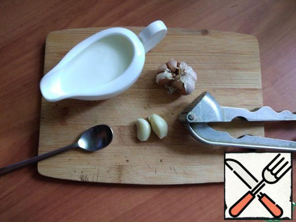 We make the sauce. Pour the yogurt into a bowl and squeeze out the garlic there. You can chop it finely.