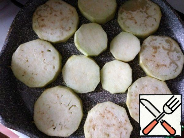 Pour the oil into a frying pan and heat it, spread the eggplant slices. I have the whole eggplant in a frying pan D-24 cm. Fry on one side.