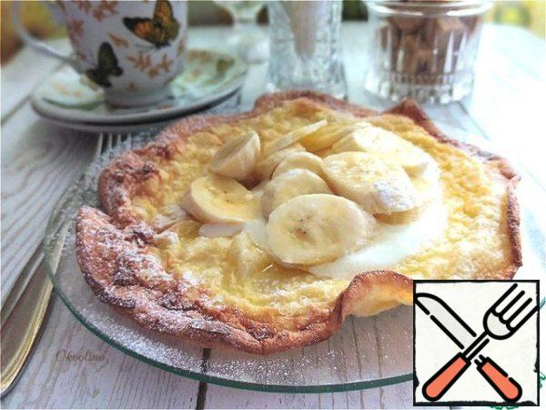 We transfer it to a plate if desired. I'll put sour cream and a chopped banana on the pancake. I'll sprinkle everything on top with powdered sugar. Eat with whatever you want!