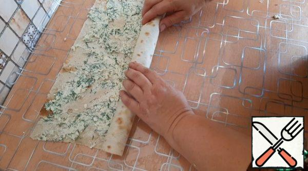We spread the filling on the pita bread, distribute it evenly. And we twist it into a roll.