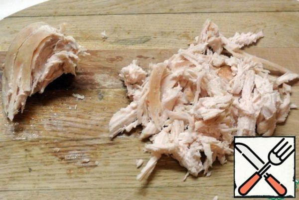 Season the chicken fillet with salt and pepper and bake in the oven. Allow to cool. Disassemble it into fibers.