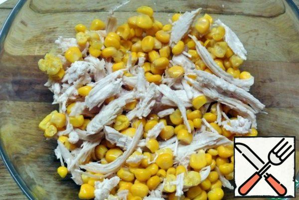 Strain the corn from the marinade. Put it in a salad bowl with chicken meat.