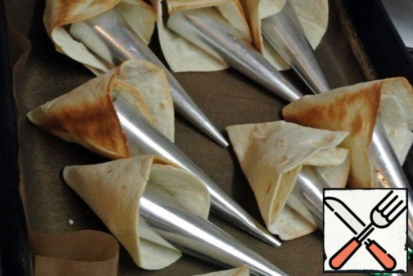 Roll up into bags. Fix it with a toothpick. Insert metal cones or foil cones inside so that the bags do not lose their shape when baking. Bake for 8 minutes at 200 C.