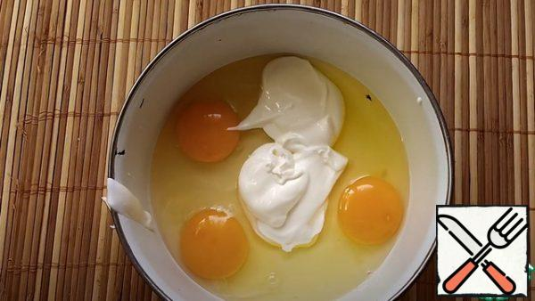 In another bowl, you need to make a batter. In a bowl, beat 3 eggs, and add sour cream 3 tbsp.  mix well.