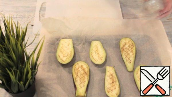 My eggplants are small, it is better to take a medium or large size for the amount of ingredients. Cut the eggplants across in strips of about 1 cm. Next, we make incisions, so they will bake faster. Lubricate the surface of the eggplant with a little vegetable oil and put it in a preheated oven to 200 degrees for about 15 minutes. Eggplants should be fully cooked.