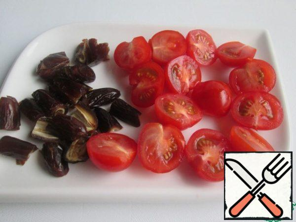 Remove the seeds from the dates and cut them into four parts. Cut the cherry tomatoes in half.