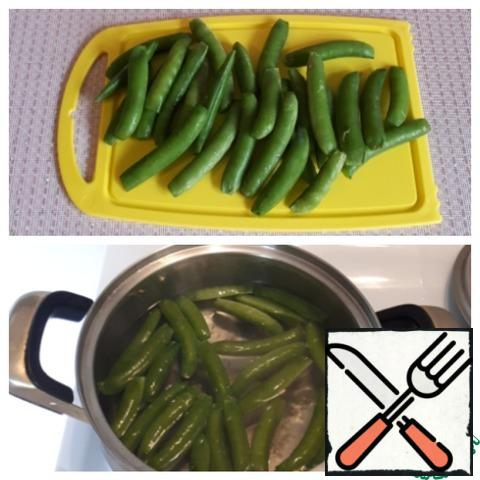 Cut off the tips of the pods of young green peas. Boil the peas for three minutes in boiling water. Put the pods on a sieve and rinse with cold water, as a result, the pods will retain their color.