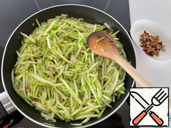 We put half of the almonds on a plate. Add the zucchini to the rest of the almonds in the pan and fry, stirring, without reducing the heat, for 5 minutes.