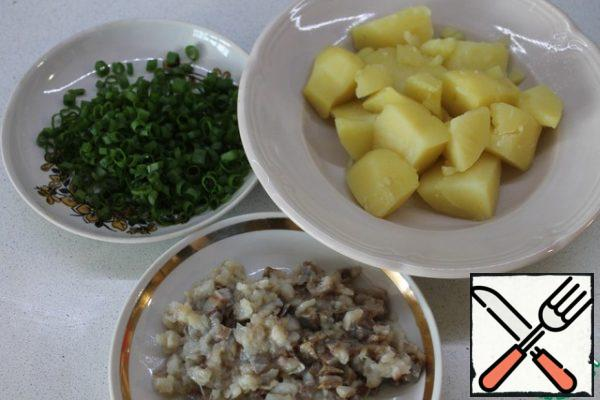 This snack is prepared very simply. Potatoes need to be cleaned, boiled, taken out of the water. Finely chop the herring and onion. Some pieces of herring should be left uncut, for decoration.