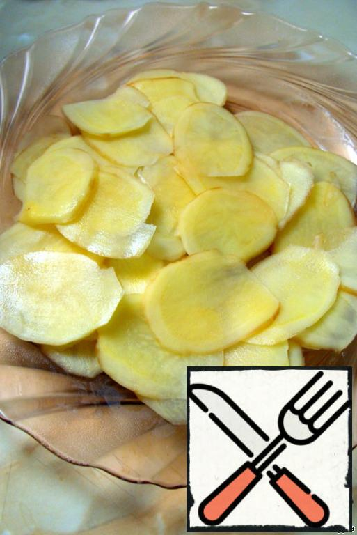 """Wash the potatoes with a brush, and whether to peel or not, decide for yourself. Cut into circles or slices as thinly as possible - it is most convenient to do this with a slicer or a special grater with a holder for the product, which cooks call """"mandolin"""". (I had a regular vegetable peeler.)"""