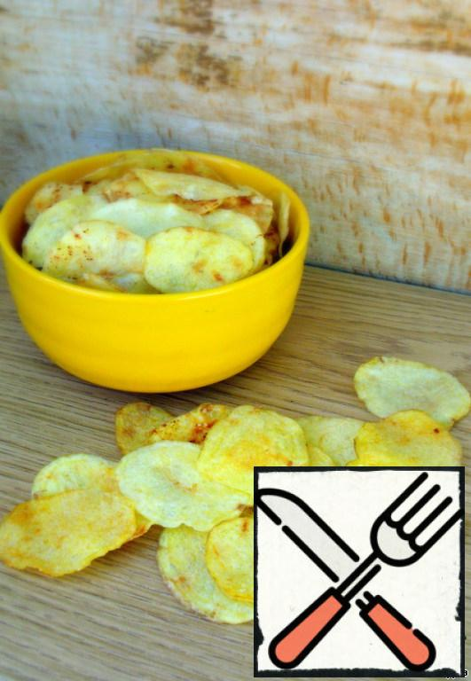 Place the potato slices in one layer on baking paper (parchment). If desired, you can add salt, add spices to your taste!!! I cooked with spices and without-and EVEN WITHOUT SALT is very tasty!!!