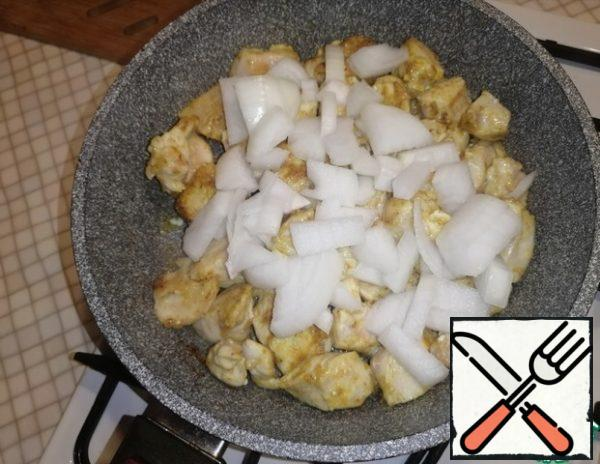 Cut the onion into large cubes, add to the pan to the chicken fillet.