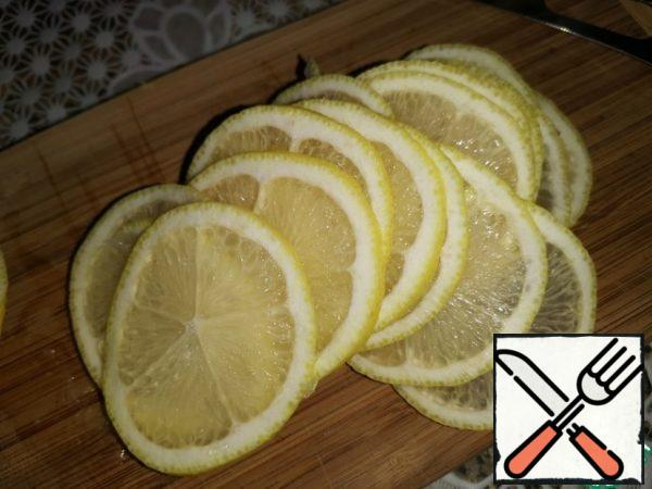 Wash the lemon thoroughly and wipe it dry. I had a large lemon, so I cut one half into thin circles, and grated the zest on the other half.