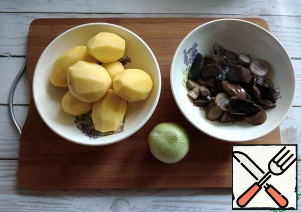 Potatoes and onions are cleaned. Mushrooms are fished out of the pan with a slotted spoon, letting the water drain.