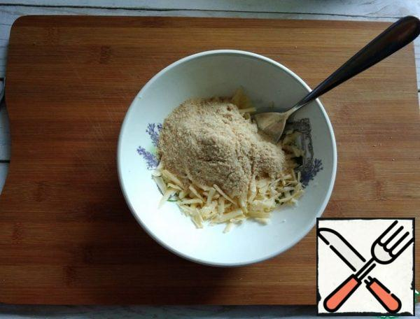 Grate the cheese and mix it with breadcrumbs.